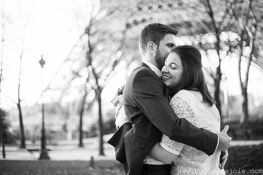 Couple d'amoureux enlacés devant la Tour Eiffel, en noir et blanc | Bulles de Joie Photographie, photographe Paris