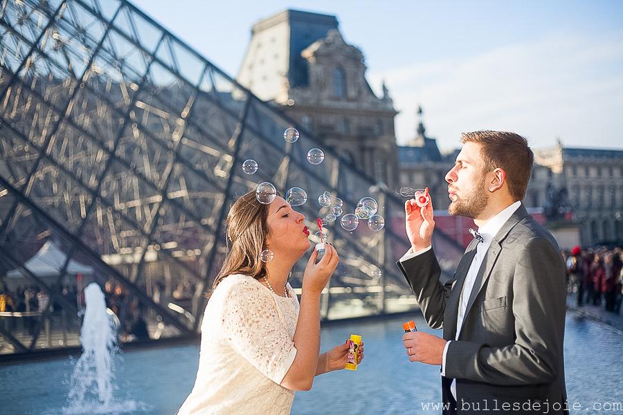 Couple jouant aux bulles de savon devant la Pyramides du Louvre | Séance photo romantique et fun | Bulles de Joie Photographie, photographe Paris