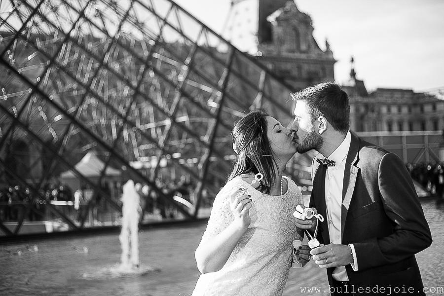 Couple s'embrassant devant la pyramide du Louvre | Bulles de Joie Photographie, photographe d'amoureux àParis