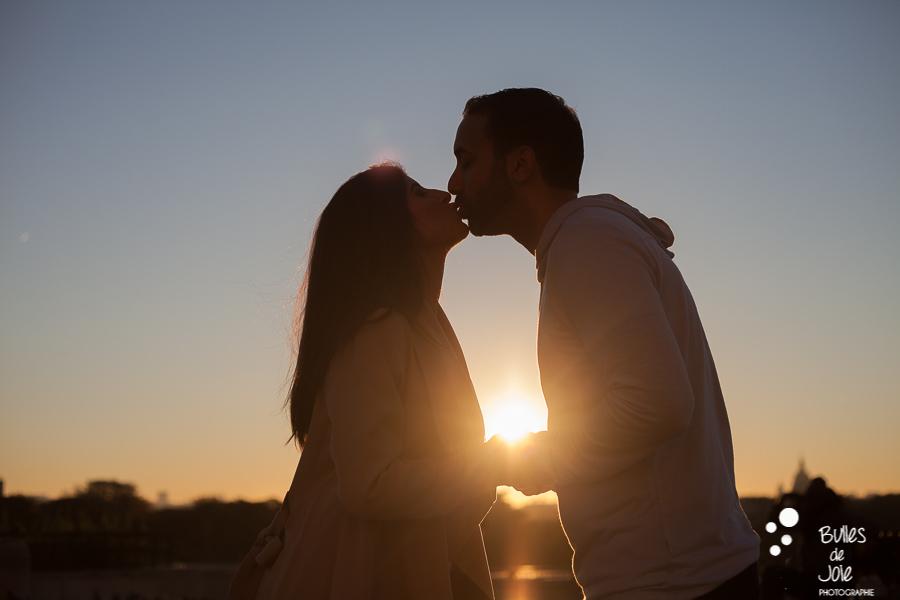 shooting photo couple : couple d'amoureux en contre-jour avec le soleil étincelant au milieu de leurs coeurs