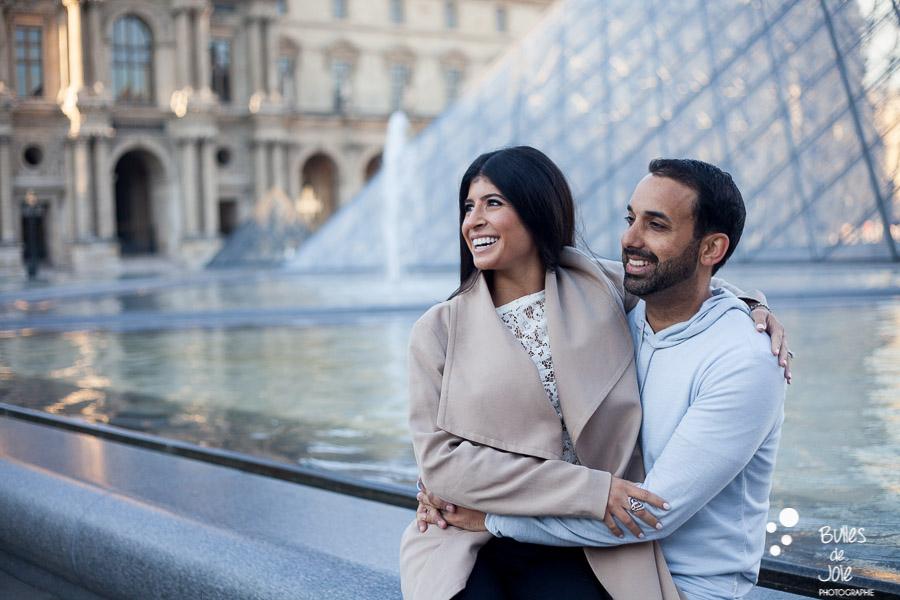 shooting photo couple : couple assis au pied de la pyramide du louvre