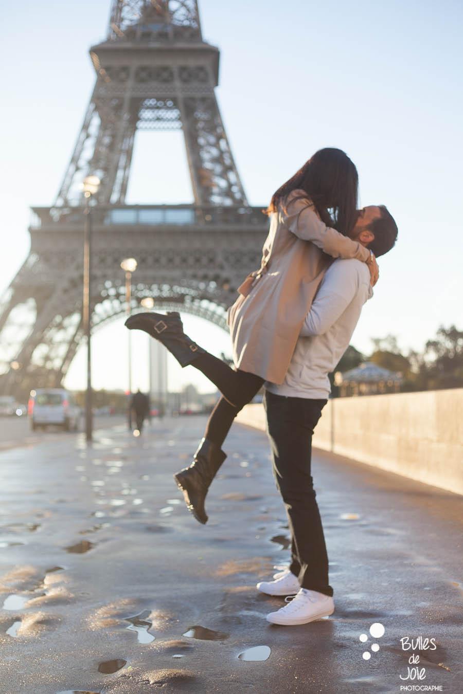 shooting photo couple : jeune homme soulevant sa femme, au pied de la Tour Eiffel