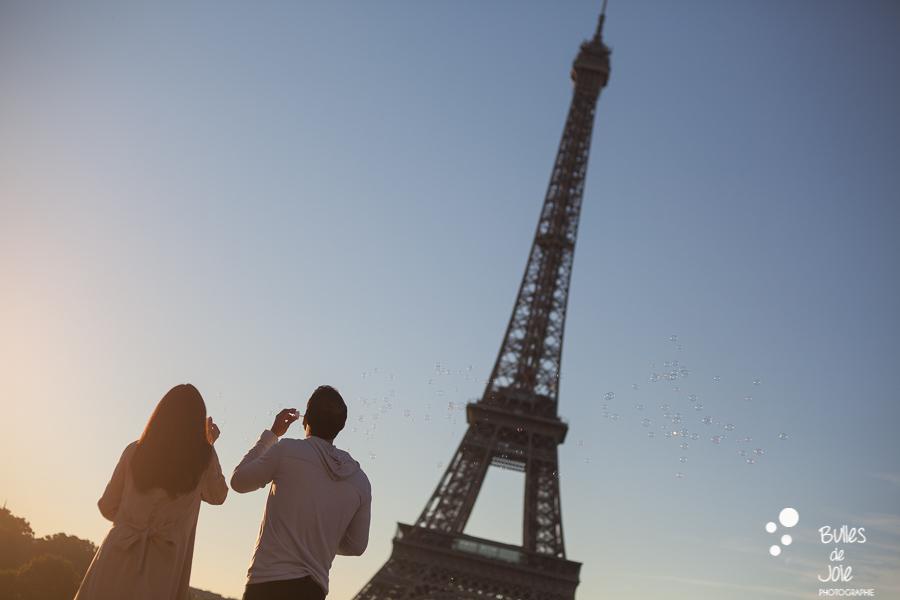 Couple au pied de la Tour Eiffel soufflant des bulles de savon
