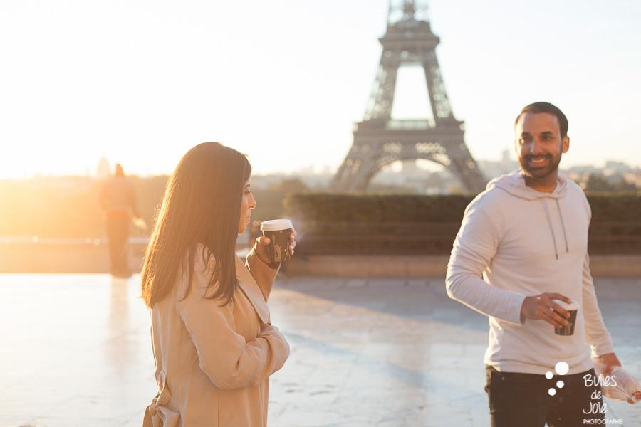 Jeune femme soufflant sur son café fumant en regardant son mari, sur le parvis du Trocadéro