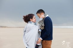 Two lovers on a beach, looking at each other. Image that illustates the blog post: seaside pregnancy photo session close to paris
