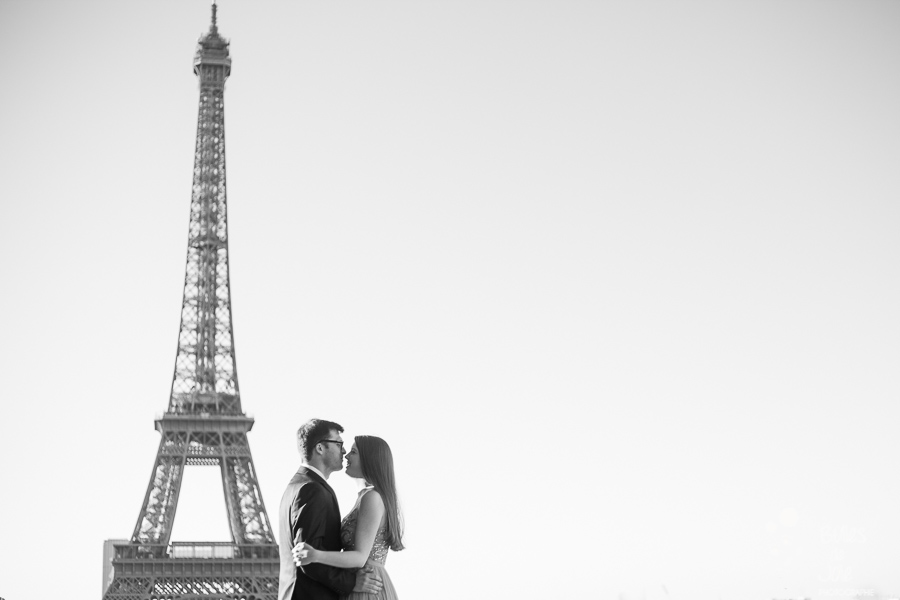 Couple kissing at the Eiffel Tower, black and white photo. Private photo shoot Paris from Bulles de Joie, professional paris photographer. More photos: