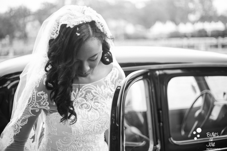 Black and white photo captured by Bulles de Joie of the bride getting in a vntage car, traction. More photos: