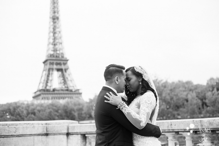 Couple in front of the Eiffel Tower on their wedding day. Black and white picture of newly weds. More photos:
