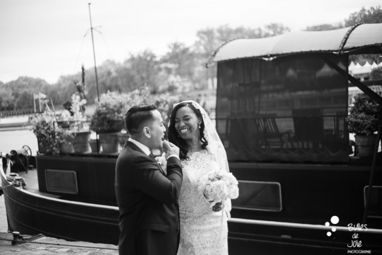 Photo session right after the vows exchange - couple walking and smiling at each other in front of a peniche on the River Seine. Photo taken by Bulles de Joie. More photos: