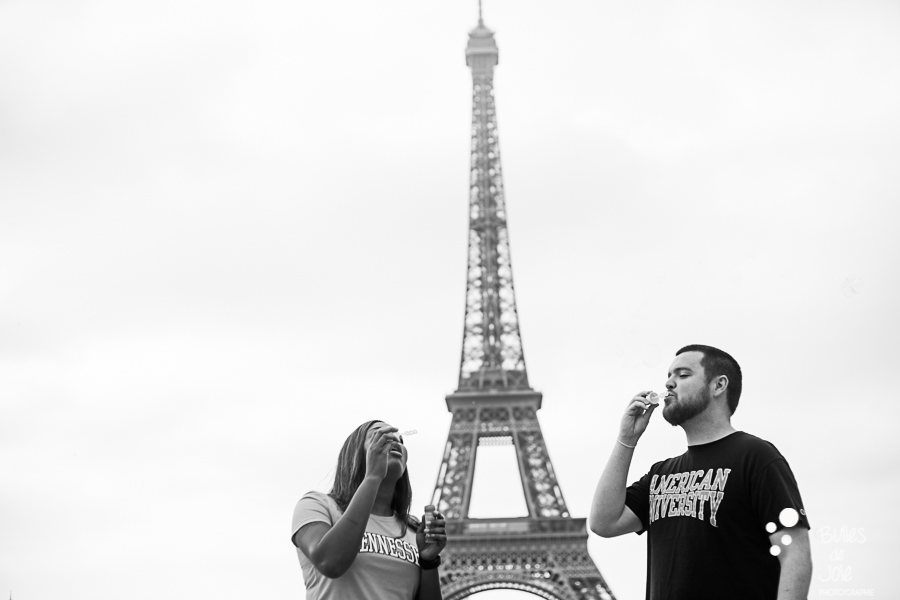 A couple blowing bubbles in front of the Eiffel Tower. Couple photo session Trocadero by Bulles de Joie, paris photographer of Happy People. More photos: