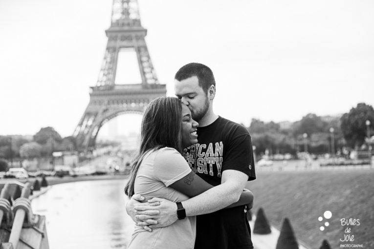 A man kissing his woman on her forehead, black and white picture. Couple photo session Trocadero by Bulles de Joie, paris photographer of Happy People. More photos: