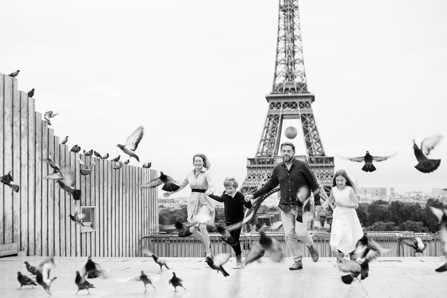 Family running and pigeons flying. In front of the Eiffel Tower. Black and white picture. Captured by Bulles de Joie, Paris family photographer.