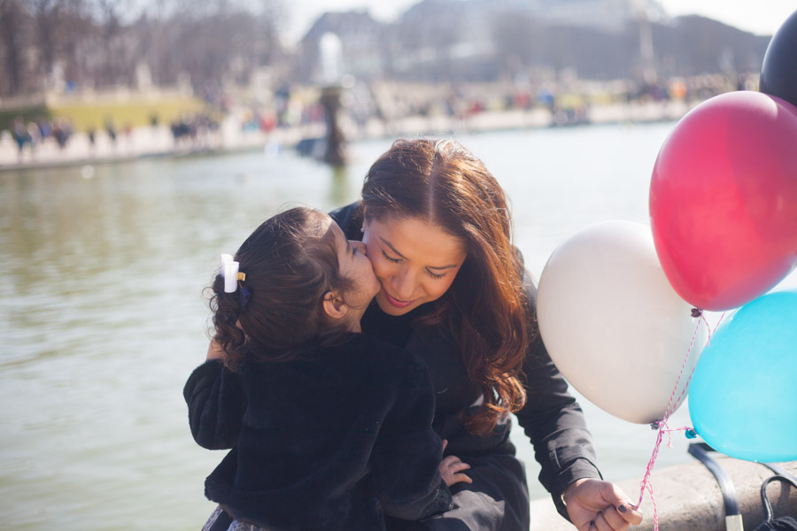 Girl with her mum holding balloons. Captured by Bulles de Joie, Paris family photographer.
