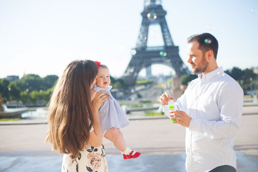 A family playing with bubbles in front of the Eiffel Tower in Paris, France. Captured by Bulles de Joie, Paris family photographer.