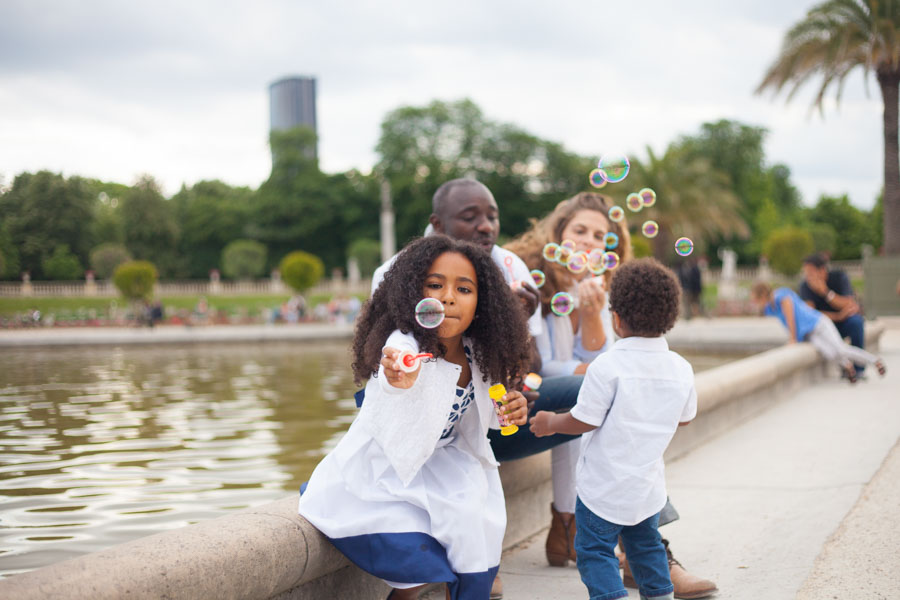 Family playing with bubbles during a family photoshoot in Luxembourg garden, Paris. Captured by Bulles de Joie, Paris family photographer.