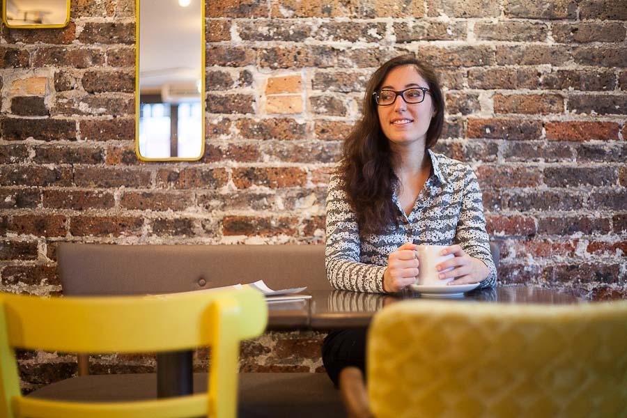 Portrait professionnel décontracté d'une entrepreneuse, dans un bar avec un mur en briques, pour une photo de profil sur un site Internet