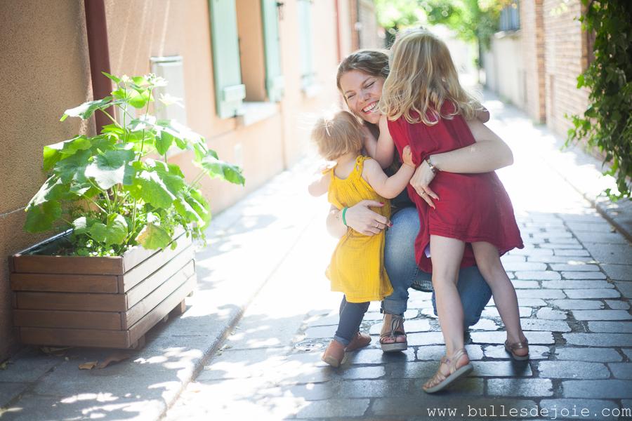Une maman accroupie serrant ses filles dans ses bras