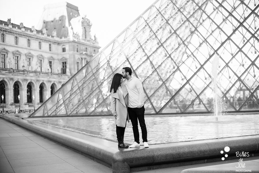 shooting photo couple : amoureux debout à l'angle de la pyramide du Louvre, photo en noir et blanc