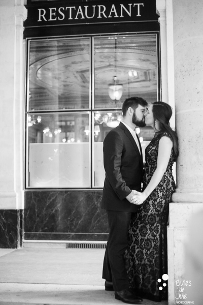Black and white portrait of a couple kissing in front of a parisian restaurant. Photo that illustrates the blog post: romantic couple photoshoot paris. More photos at: https://www.bullesdejoie.net/2017/03/06/romantic-couple-photoshoot-paris/