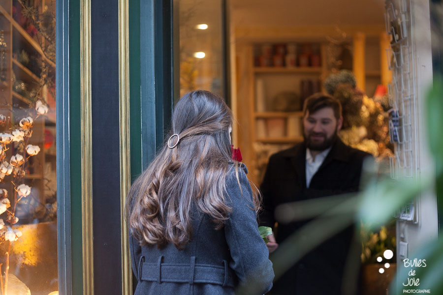 A woman looking inside a shop to see her husband. Romantic couple photoshoot paris by Bulles de Joie, photographer of Happy People in Paris. More photos at: https://www.bullesdejoie.net/2017/03/06/romantic-couple-photoshoot-paris/
