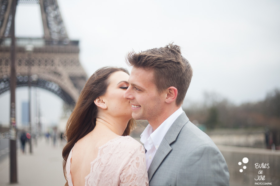 A woman kissing her boyfriend on his cheek. More photos of this love session paris at the following link: