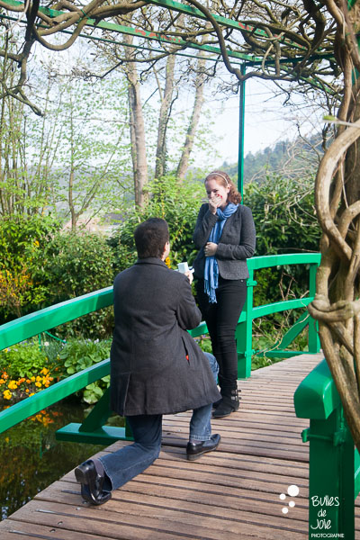 Man on his knee to propose her girlfriend in the famous bridge of Monet's Garden. More photos of the proposal at: https://www.bullesdejoie.net/2017/04/25/romantic-proposal-monets-garden-giverny-france/