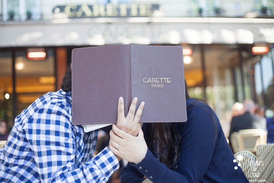 Lovers hidding their kiss with the menu of a cafe. Portrait illustrating the blog post created by Bulles De Joie, professional photographer in Paris on the blog post: photos for couples in Paris. More photos: