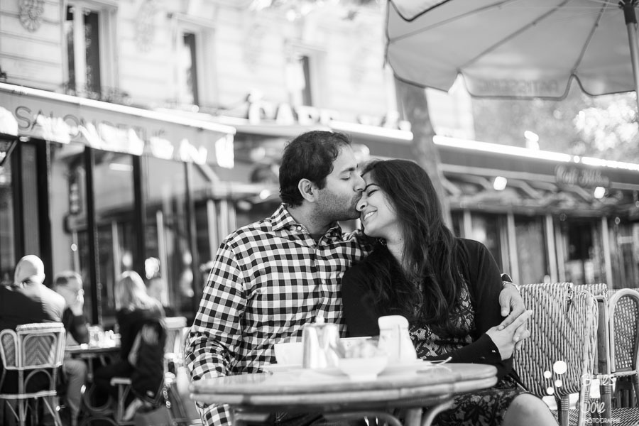 Black and white portrait of a man kissing his wife at a parisian cafe. Romantic photo illustrating the blog post created by Bulles De Joie, professional photographer in Paris on the blog post: photos for couples in Paris. More photos: