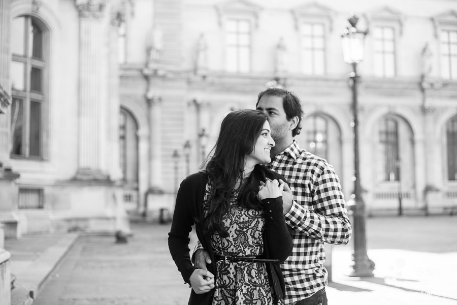Black and white photo of a man kissing his wife on the forehead at the Louvre. Portrait illustrating the blog post created by Bulles De Joie, professional photographer in Paris on the blog post: photos for couples in Paris. More photos: