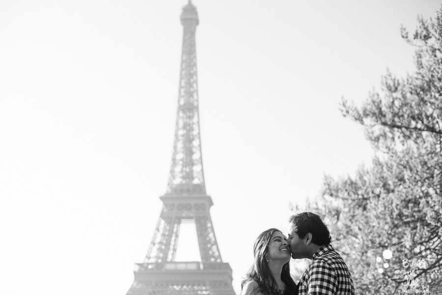 A man kissing his wife on her cheek in front of the Eiffel Tower. Black and white portrait illustrating the blog post created by Bulles De Joie, professional photographer in Paris on the blog post: photos for couples in Paris. More photos: