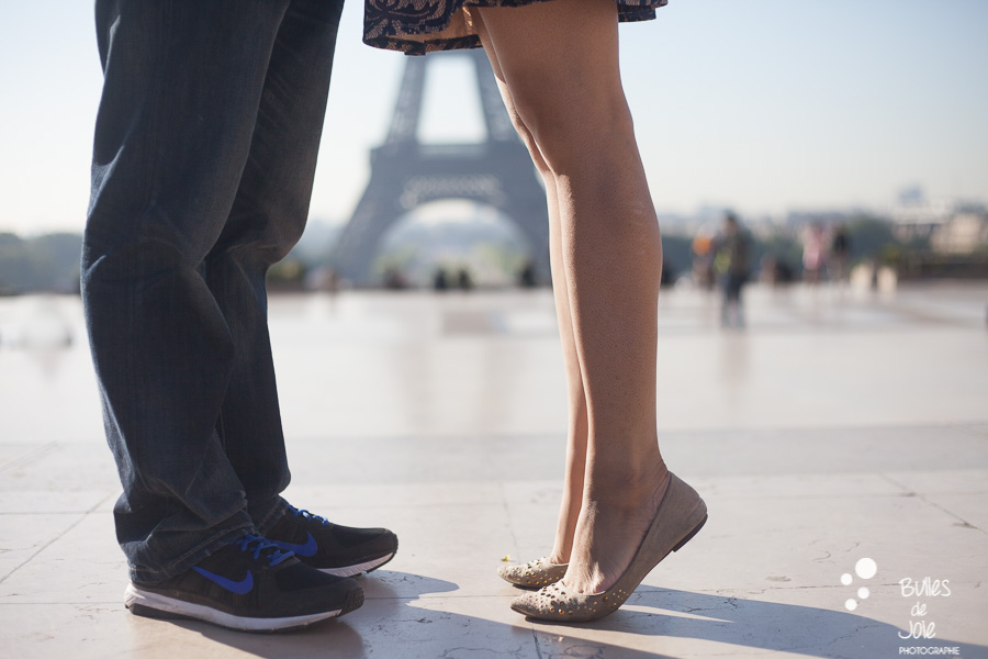 Lovers' feet in front of the Eiffel Tower. Portrait illustrating the blog post created by Bulles De Joie, professional photographer in Paris on the blog post: photos for couples in Paris. More photos: