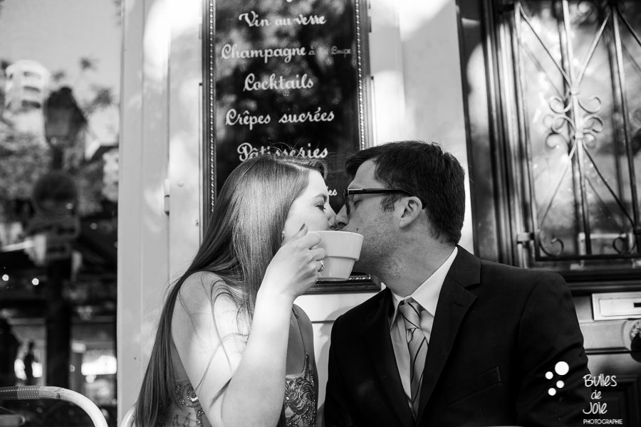 Hidden kiss with a cup at a parisian cafe. Private photo shoot Paris captured at Montmartre by Bulles de Joie, professional paris photographer. More photos: