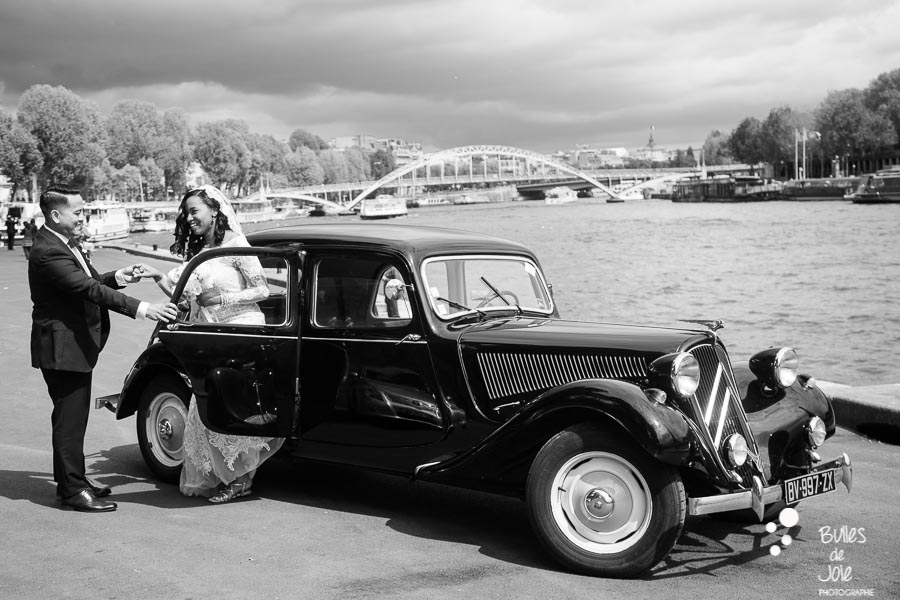 Parisian elopement: bride getting out of a vintage car (traction). Black and white photo by Bulles de Joie. More photos:
