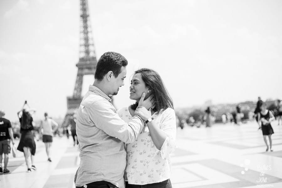 Couple kissing in front of the Eiffel Tower. Black and white photo captured by Bulles de Joie, professional photographer in Paris. More photos: