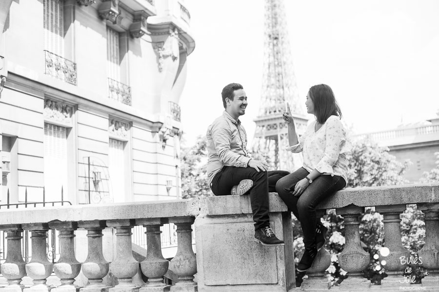 Couple playing in front of the Eiffel Tower. Candid photo captured by Bulles de Joie, professional photographer in Paris. More photos:
