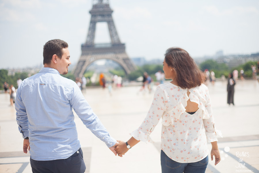 Engagement photoshoot in Paris - Woman and man walking on the Trocadero hand in hand - Photo taken by Bulles de Joie, photographer of Happy People in Paris. More photos: