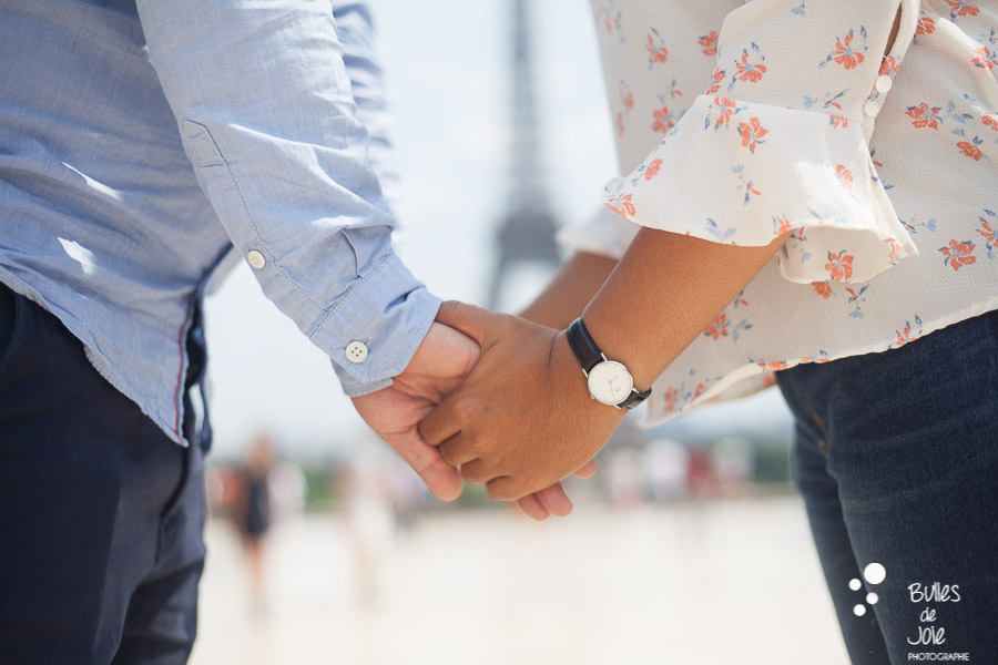 Engagement photoshoot in Paris - Woman and man holding their hands, on the Trocadero, in front of the Eiffel Tower - Photo taken by Bulles de Joie, photographer of Happy People in Paris. More photos: