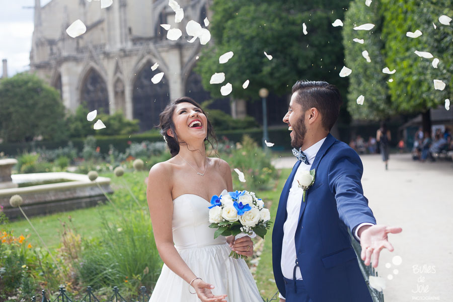 Bride and groom launching flowers into the air at the end of their wedding ceremony at Notre-Dame, Paris. More photos: