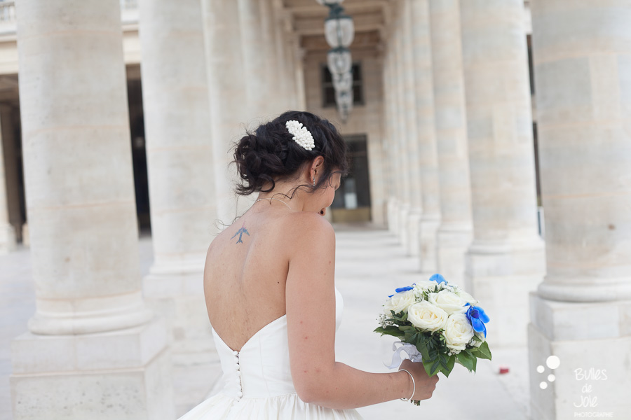 Bride in her white dress, holding her bouquet, at Palais-Royal Gardens. More photos:
