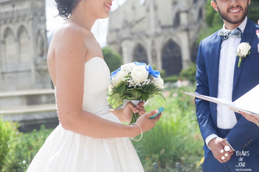 Woman and man during their elopement ceremony. Woman holding her white and blue bouquet. More photos at: