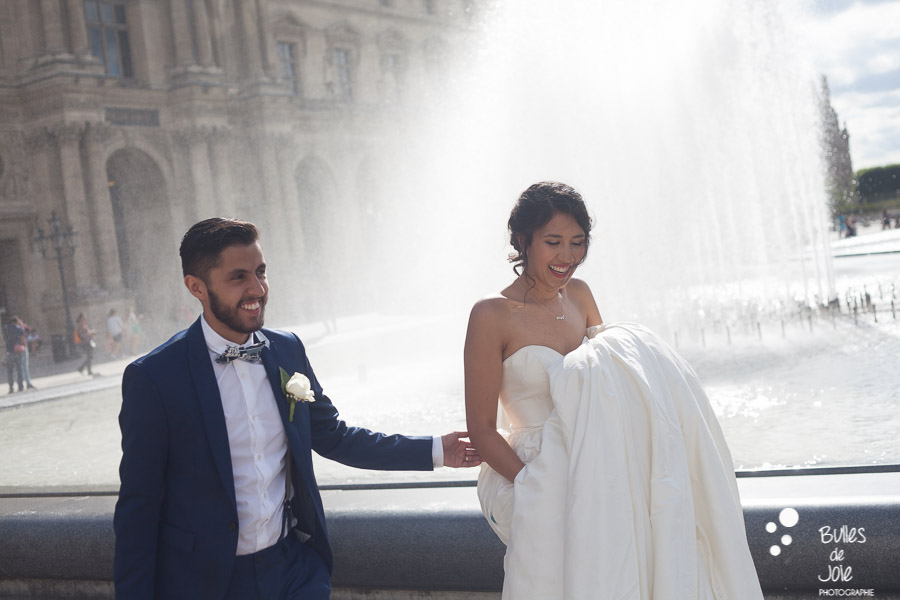 Bride and groom surprised by the water at the Louvre. Elopement in Paris by Bulles de joie, photographer of Happy People in Paris. More photos