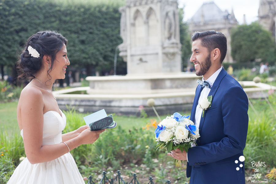 Woman reading her vows to her husband. Outside ceremony for an elopement in Paris at Notre-Dame Cathedral. More photos at: