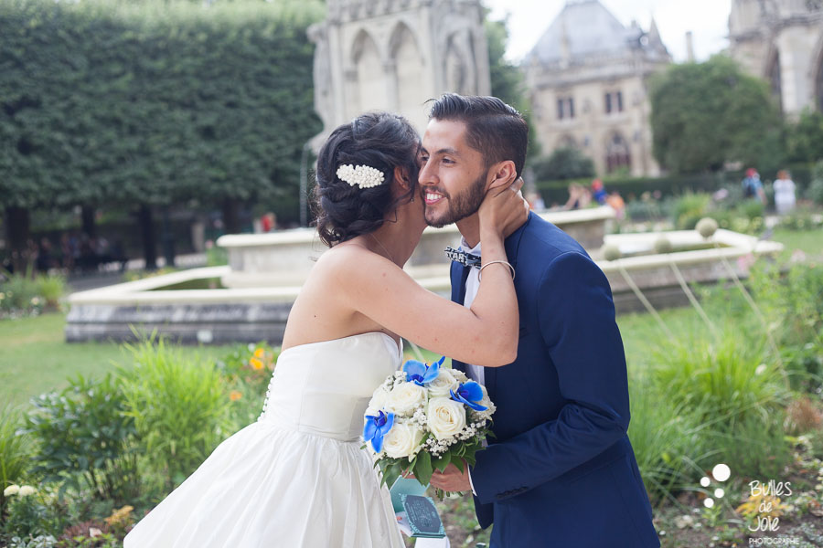 Woman and man kissing on the cheek after their vows. Outside ceremony at Notre-Dame. More photos at: