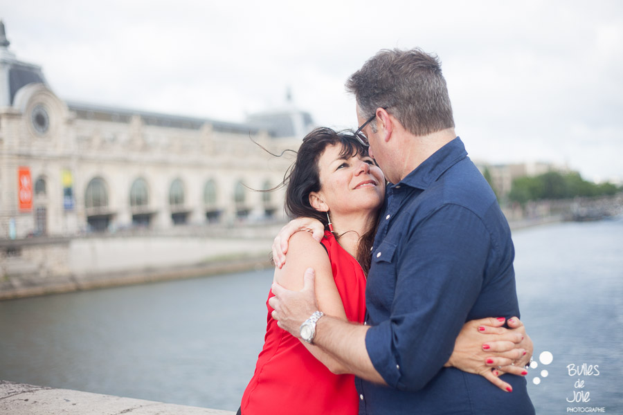 Couple holding each other with Musee du Quai d'Orsay in the background. More photos: https://www.bullesdejoie.net/en/2017/07/13/paris-love-session-25th-anniversary/