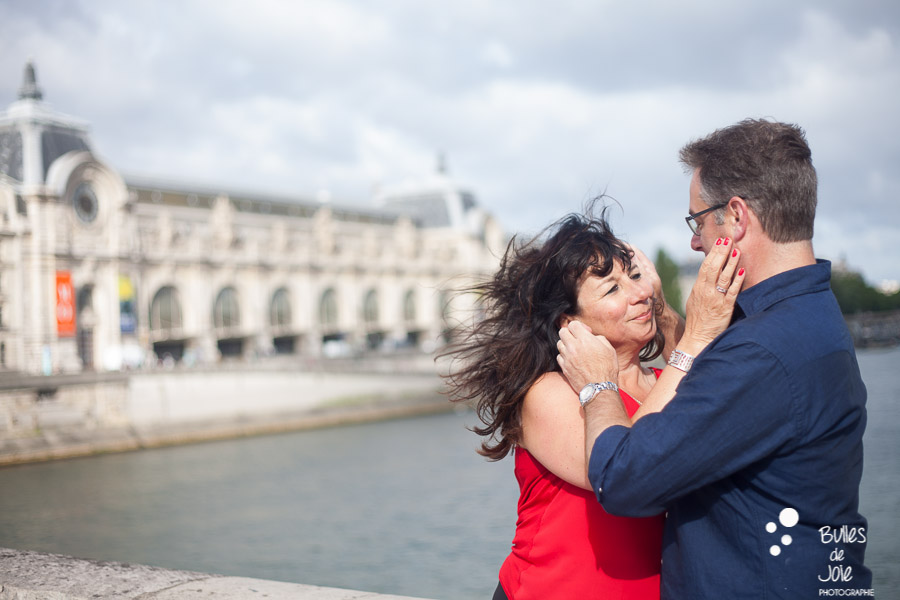 Couple caressing each other face with Musee du Quai d'Orsay in the background. More photos: https://www.bullesdejoie.net/en/2017/07/13/paris-love-session-25th-anniversary/