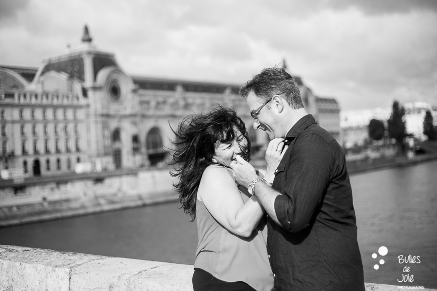 Black and white photo of a couple caressing each other face with Musee du Quai d'Orsay in the background. More photos: https://www.bullesdejoie.net/en/2017/07/13/paris-love-session-25th-anniversary/