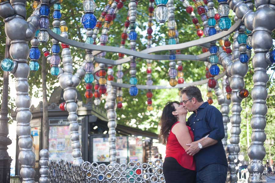 25th wedding anniversary. Photoshoot of two lovers kissing under a colorful piece of art in Paris. Photoshoot in hidden gems in Paris, by the photographer of Happy People: Bulles de Joie. More photos: https://www.bullesdejoie.net/en/2017/07/13/paris-love-session-25th-anniversary/