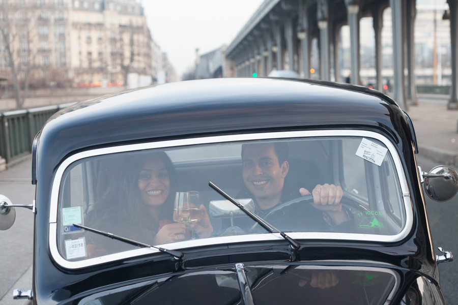 Lovers smiling to the camera, in a beautiful black vintage car in Paris. Photo captured by Bulles de Joie, Engagement & family photographer in Paris.