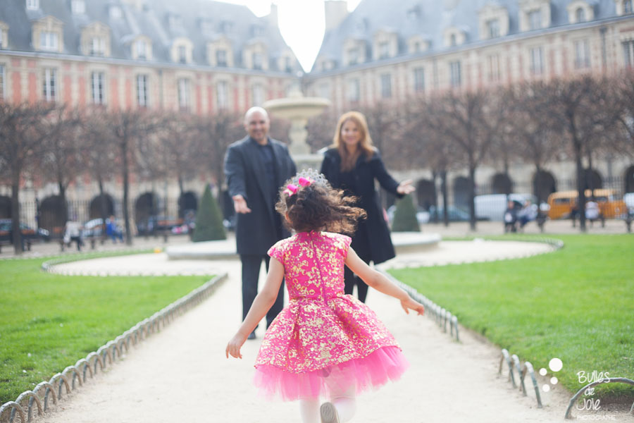 Little girl wearing a pink dress running into her parents. Paris family photo session made by Bulles de Joie. More photos: