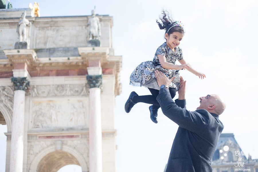 A dad holding her girl into the air, which makes her laugh. Paris family photographer: Bulles de Joie. More photos: